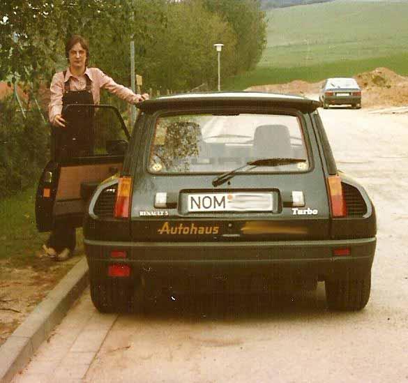 Eine junge Frau steht neben einem Sportwagen.