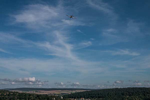 Ein Sportflugzeug verschwindet im blauen Himmel über einer Landschaft.