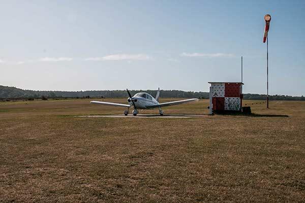 Auf einem kleinen Flugfeld steht eine Cherokee-Maschine.