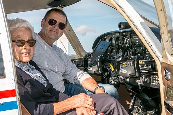 Ein Pilot und eine andere Dame sitzen in einem Kleinflugzeug.