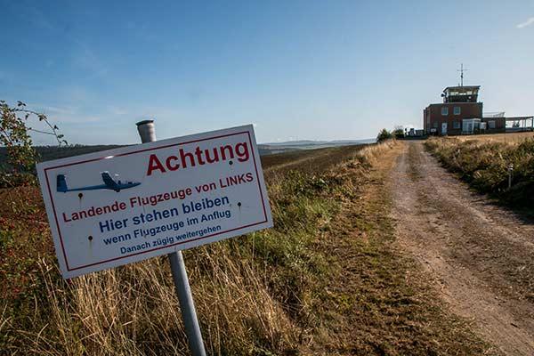 Ein Schild warnt davor, dass von links ein Flugzeug kommen könnte.