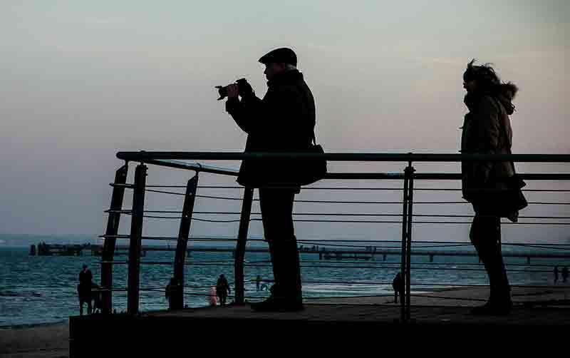 Fotograf am Strand mit Ehefrau