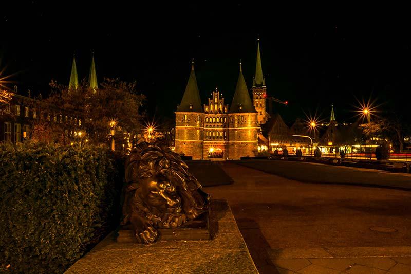 Der linke Löwe vor dem Lübecker Holstentor, aufgenommen bei Nacht.