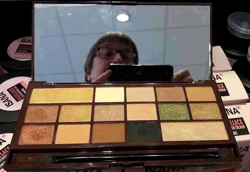 Eine Palette mit Liedschatten, darüber ein Spiegel mit einem halben Gesicht.