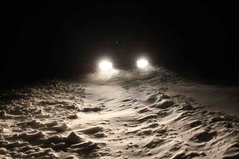 Ein Auto steckt im dunkeln in einer Schneewehe fest.